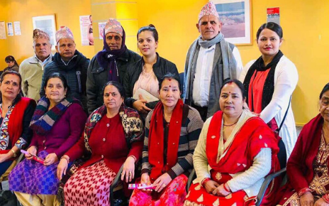 A row of seated Nepalese women and a row of standing men and women behind them.