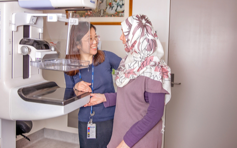Radiographer and client in front of a mammogram machine.