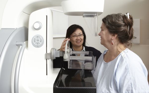 Radiographer with a woman having a breast screen.