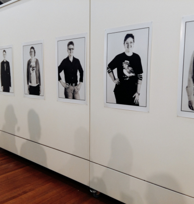 Black and white portraits of women on a wall in an art gallery.